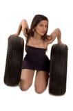 Tire. Young sexy girl holding a car wheel Stock Photos