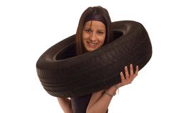 Tire. Young sexy girl holding a car wheel Stock Images