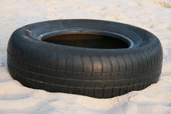 Tire. Black tire on the sand Royalty Free Stock Images