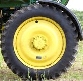 Tire. Large rear rubber tractor tire on yellow painted rim Royalty Free Stock Photos