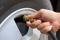 Tire air pressure checking before traveling Royalty Free Stock Images