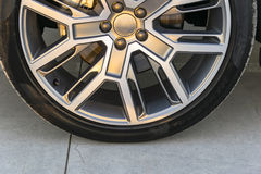 Tire and alloy wheel of a modern car on the ground, car exterior details Stock Image