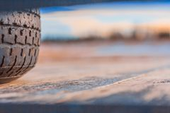 Tire on the Back of a Flatbed Truck. Section of a car tire on the back of a wooden flatbed truck with a blurred field and sky background royalty free stock photography