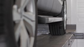 Tire balancing, wheel alignment, professional car maintenance. Machine repair and tire inflation, Car on stand for wheels alignment camber check in workshop of stock footage
