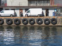 Tire boat bumpers in Copenhagen. COPENHAGEN, DENMARK - CIRCA AUGUST 2017: Old tire line on a stone wharf Stock Image