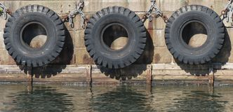 Tire boat bumpers. Old tire line on a stone wharf in Copenhagen, Denmark Royalty Free Stock Photo