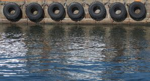 Tire boat bumpers. Old tire line on a stone wharf in Copenhagen, Denmark Stock Photos