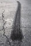Tire Burnout on Asphalt. A rear tire burnout or skid mark on old cracked asphalt Stock Images