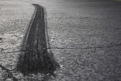 Tire Burnout on Asphalt II. A rear tire burnout or skid mark on old cracked asphalt Royalty Free Stock Photography