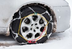 Tire chains on car in snow. Front view of tire chains on car wheel on dirty vehicle in snow royalty free stock images