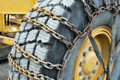 Tire chains on road grader Stock Photo