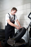 Tire change. Mechanic deflating vehicle tyre in car service Royalty Free Stock Image