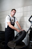 Tire change. Mechanic deflating vehicle tyre in car service Stock Image