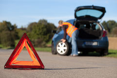 Tire change. On a broken down car with a red warning triangle stock images