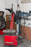 Tire changer device in an automobile repair shop. A tire changer device in an automobile repair shop, with a wheel balancing machine in the background Royalty Free Stock Image