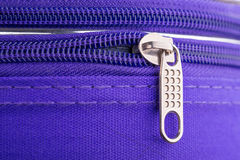 Tire de la etiqueta y de la cadena de una cremallera en Violet Suitcase Foto de archivo
