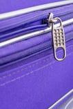 Tire de la etiqueta y de la cadena de una cremallera en Violet Suitcase Fotos de archivo