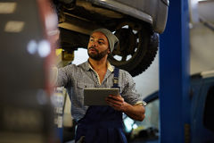 Tire diagnostics. Repairman with touchpad making tire diagnostics royalty free stock image