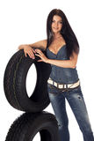 Tire and disk. Young sexy girl lying near the car wheel and disk, isolated on white Royalty Free Stock Image