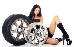 Tire and disk. Young sexy girl lying near the car wheel and disk,  on white Stock Photo