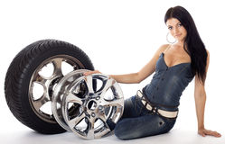 Tire and disk. Young sexy girl lying near the car wheel and disk,  on white Stock Images