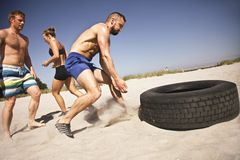 Tire flip crossfit exercise on beach. Strong male athlete about to flip a truck tire. Young people doing crossfit exercise on beach on a sunny day royalty free stock photo