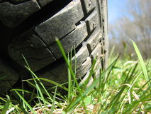Tire on grassy ground. Close-up of a tire on grassy ground Stock Image