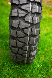 Tire at green grass Royalty Free Stock Image