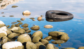 Tire in lake Royalty Free Stock Photos