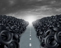 Tire Landfill Concept. Tire or tyre landfill automotive transportation concept as a heap of black rubber wheels stacked high with a clear road path as a car Stock Photography