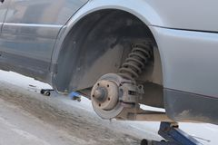 Closeup of part of gray old car without wheel. Tire mounting or brake system repair royalty free stock photo