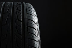 Tire. New tire, just bought , on an isolated dark background Royalty Free Stock Images