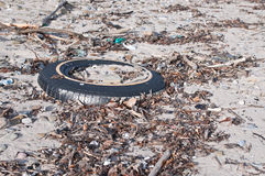 Tire and Other Litter on a Beach Royalty Free Stock Images
