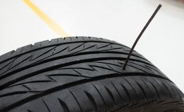 Tire pierced by iron stick or nail. Car accident or safety insurance concept Stock Images