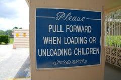 Tire por favor adelante al cargar o descargando a niños firme Fotografía de archivo libre de regalías