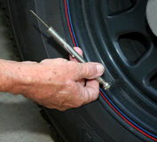 Tire pressure check. Man's hand holding gauge, verifying tire pressure on an automobile, in order to increase miles per gallon Stock Photo