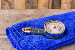 Tire pressure gauge and microfiber cloth on wooden table Stock Photo