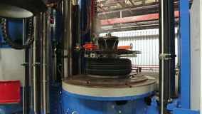 Automotive wheel molding in a factory. Tire production machine close up. Hot, smoked tires after molding arrive on the conveyor. Automotive wheel molding in a stock video footage