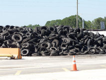 Tire Recycling. Pile of rimless tires on Recycle Alley at a landfill. The sign for tires with rims can be seen Stock Image