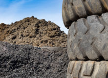 Tire recycling industry. Close up of old used tires and shredded tire pile in background stock image