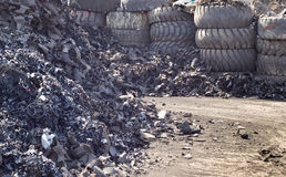 Tire recycling industry. Close up of shredded tire pile and old used tires in background stock image