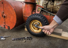 Tire Repair. Close up of a hand removing snow blower bolts to replace a tire Royalty Free Stock Image