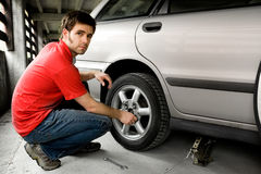 Tire Repair. A male chaning a tire on a car stock photo