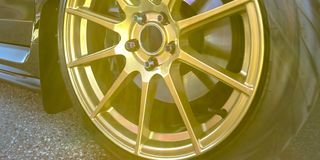 Tire rim with disc brake seen between gold spokes. Tire rim of a shiny black car on a sunny day. The silver disc brake on the wheels can be seen between the royalty free stock photos