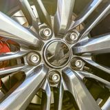 Tire rim with disc brake showing between spokes. Close up on a silver tire rim of a car with glassy center cap and five silver bolts. The disc break and pad stock image