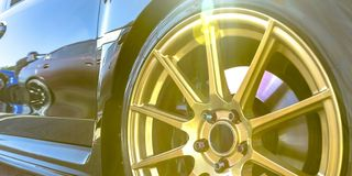 Tire rim with golden spokes of a reflective car. Wheel rim of a car with disk brake visible between the golden spokes. Reflection of other cars can be seen on stock images