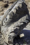 Tire rubber pollution. Old deformed tractor tyre posing a threat. To the environment. Example of modern toxic waste at the centre of environmental concern Royalty Free Stock Photo
