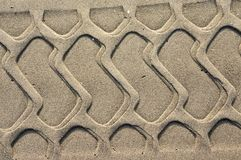 Tire sample in the sand. Background with beige fine sand. Sand surface on the beach, view from above. royalty free stock images