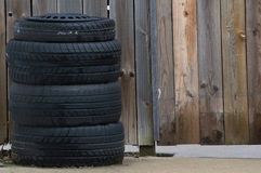 Tire stack. A stack of tires in front of a wet wooden fence Stock Photography