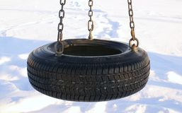 Tire swing. Swing made of tire in the middle of snow royalty free stock image